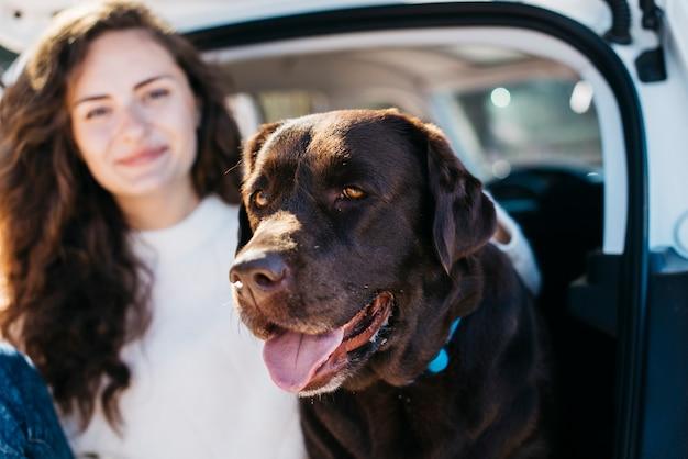 Женщина сидит со своей собакой в открытом багажнике