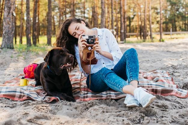 自然の中で彼女の犬と一緒に座っている女性