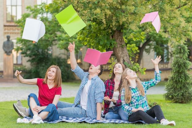 空気中の本を投げる学生のグループ