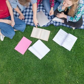 草の上の本を持つ学生のトップビュー