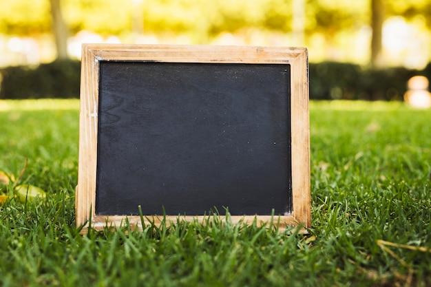 緑の芝生の上に空の黒板