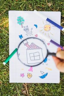 子供の緑の芝生の上の拡大鏡を通して描く