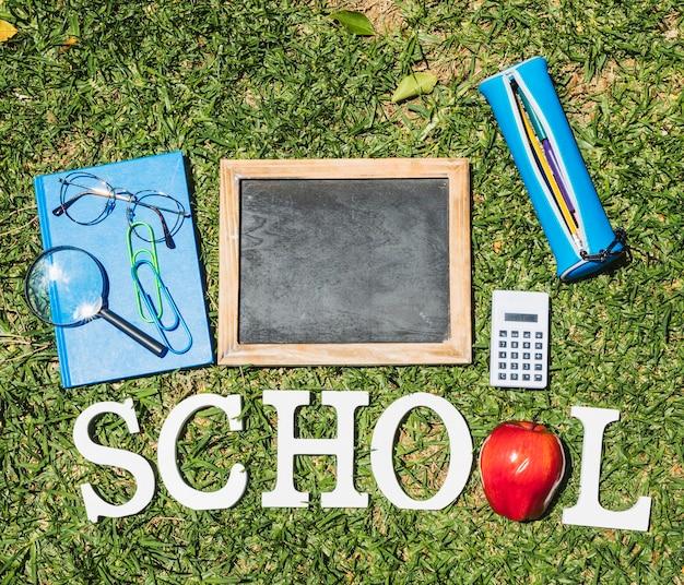 草の上の文房具の横にあるワードスクール