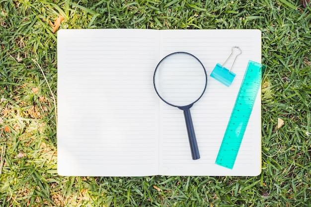 草の上の拡大鏡とノートブックを開く