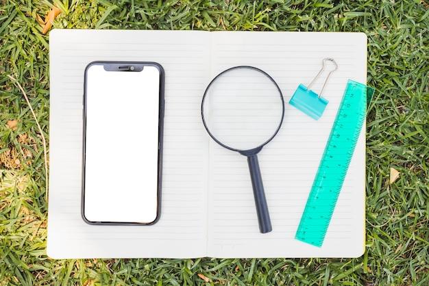開かれたノートブックの上にスマートフォンと拡大鏡