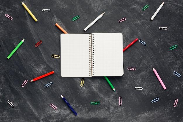 鉛筆とペーパークリップの近くに開いたノート