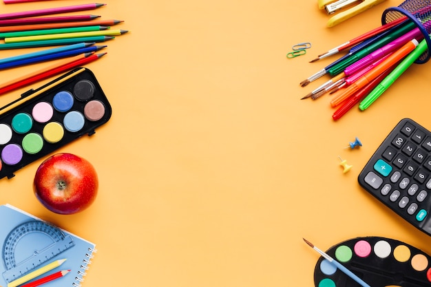 Школьные принадлежности разбросаны на желтом столе