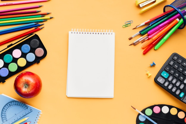 黄色の机の上の空白のメモ帳の周りに散らばって多色学校文房具