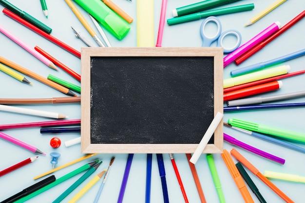 青い机の上の空白の黒板の周りに散らばって様々な描画ツール