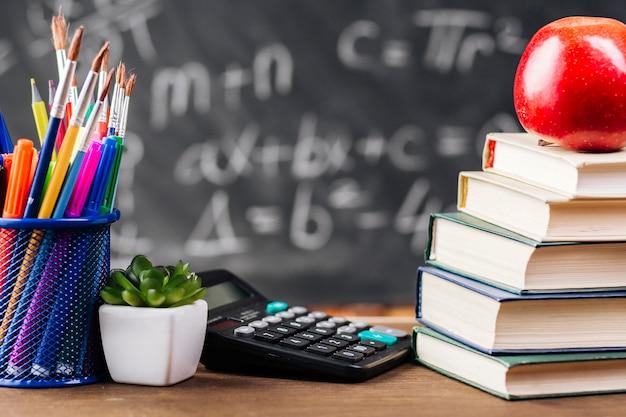 Книги и канцелярские товары на учительском столе