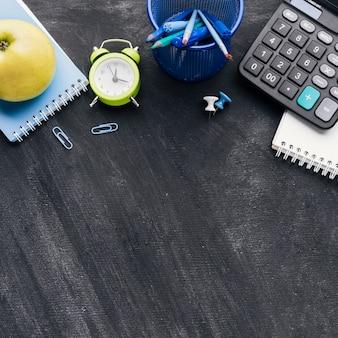 Канцелярские товары, калькулятор и яблоко на сером фоне