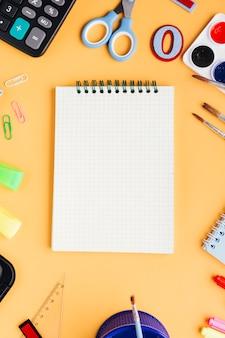 ベージュ色の背景に文房具に囲まれた白い新しいノート