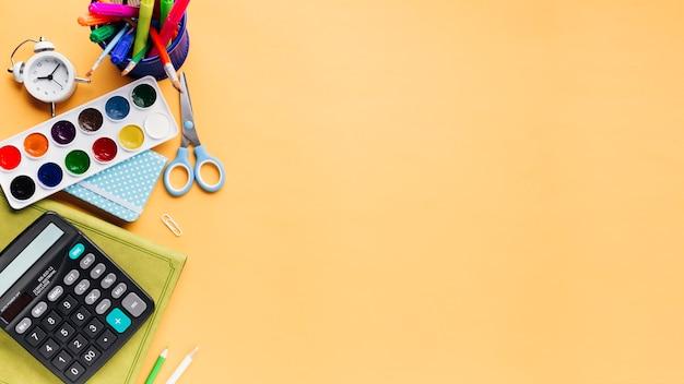 ベージュ色の背景上の創造的な明るい文房具