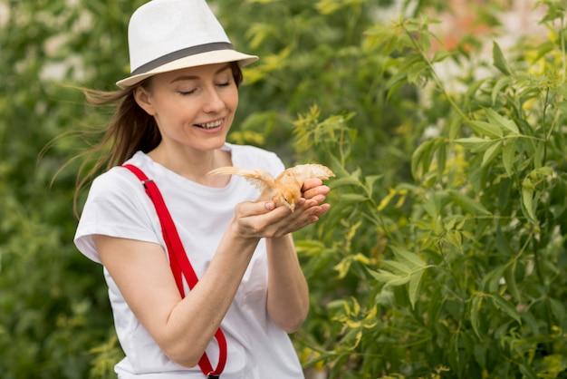 農場でひよこを保持している女性