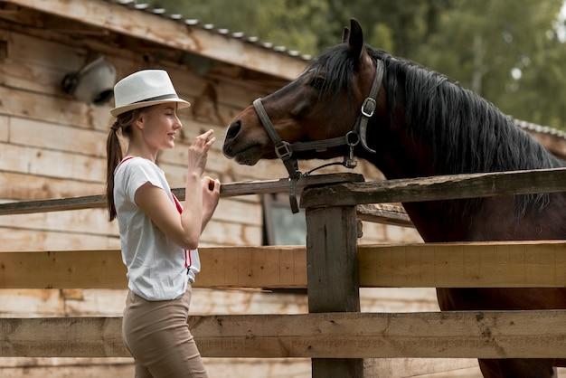 馬小屋で馬を持つ女性