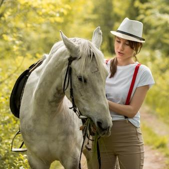 Женщина гуляет с лошадью в сельской местности