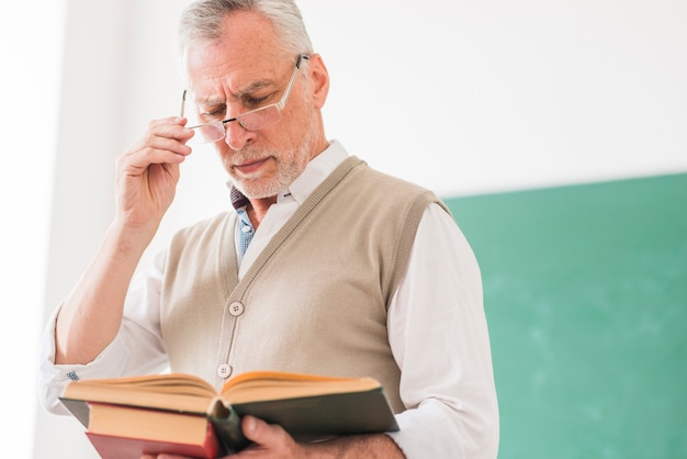 Старший мужчина профессор читает книгу, исправляя очки