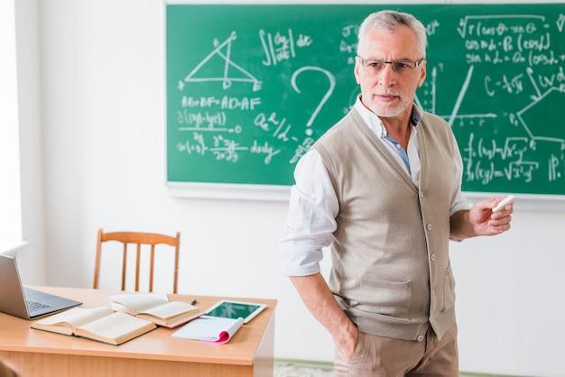 Пожилой учитель человек с мелом, объясняя математику