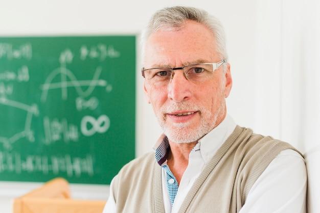 Внимательный пожилой учитель математики в очках
