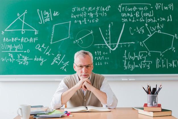 Строгий учитель смотрит в камеру в классе