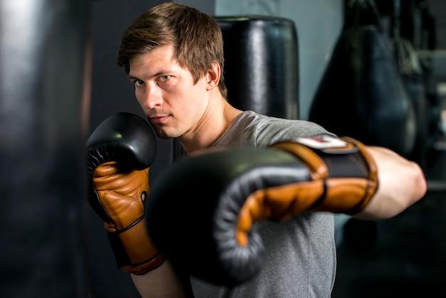 Мальчик боксер позирует в тренажерном зале