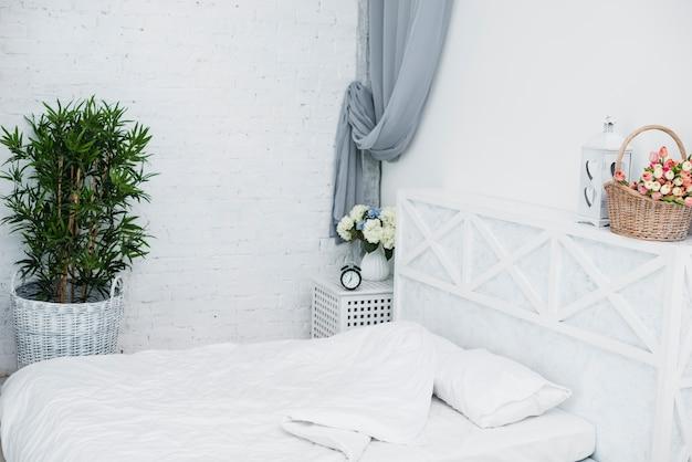 白い寝室の年配のカップルのベッド