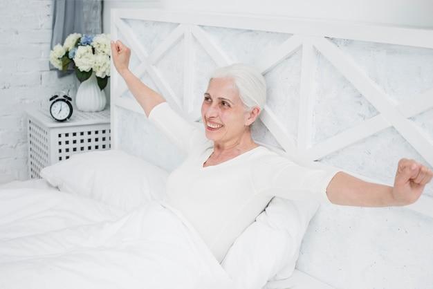 年配の女性がベッドで目を覚ます