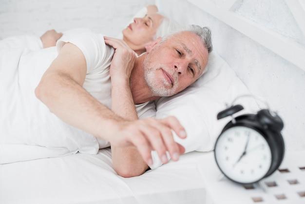 Пожилая пара отдыхает в постели