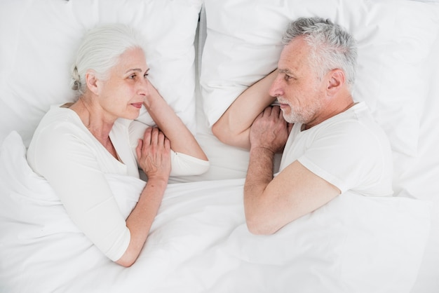 年配のカップルがベッドで休んで