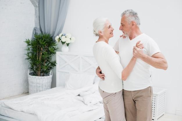 寝室で踊る年配のカップル