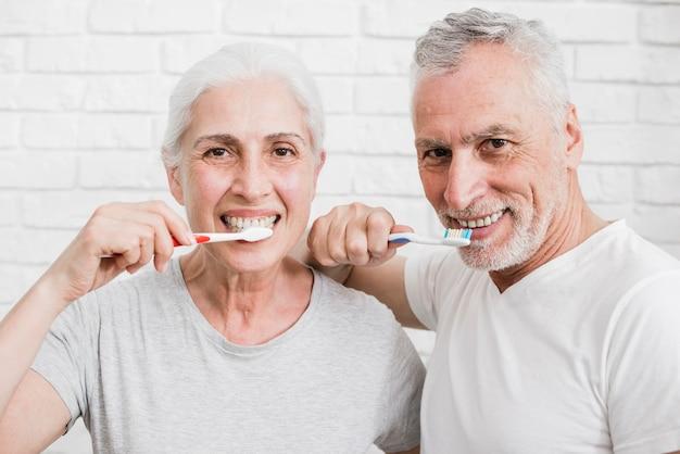 Пожилая пара моет зубы