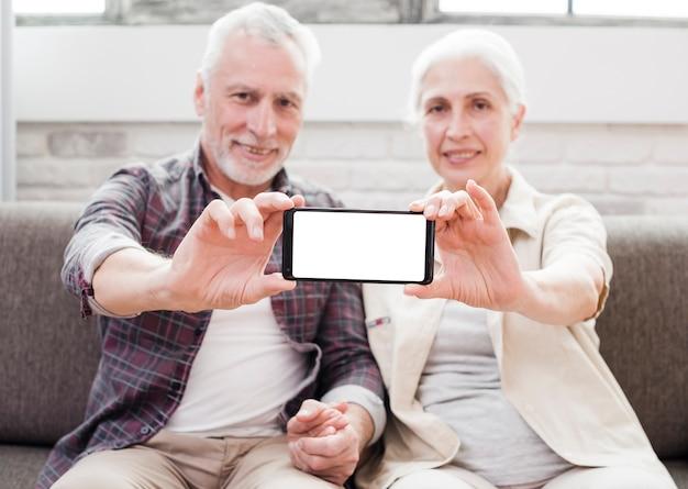 Пожилая пара показывает смартфон