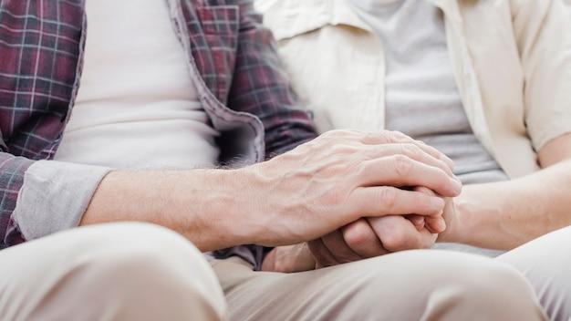 Пожилая пара держит руки