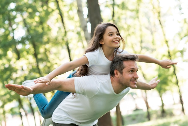 Счастливый человек, давая контрейлерных его красивая дочь с руками, вытянутыми в парке