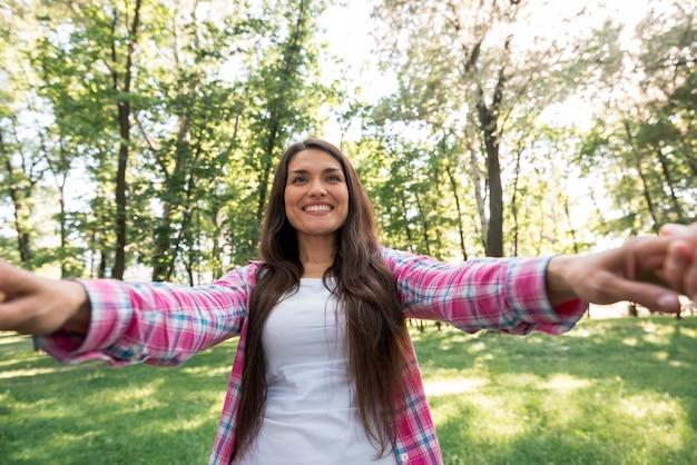公園で彼女のパートナーの手を引いて笑顔の女性