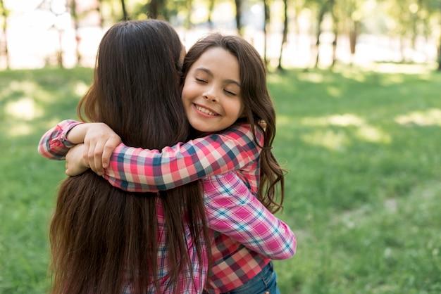 目を閉じて公園で彼女の母親を抱いて笑顔のかわいい女の子