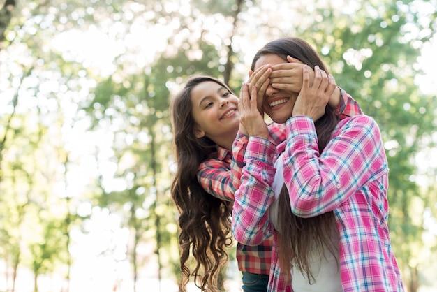 彼女の母親の目を手で覆っている陽気な女の子