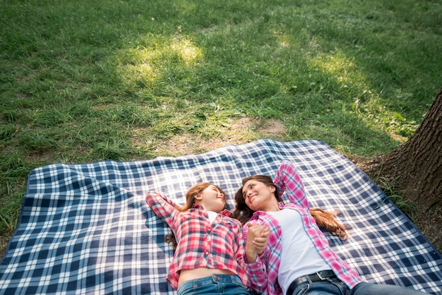 母と娘が公園で毛布の上に横たわる自分の手を握って