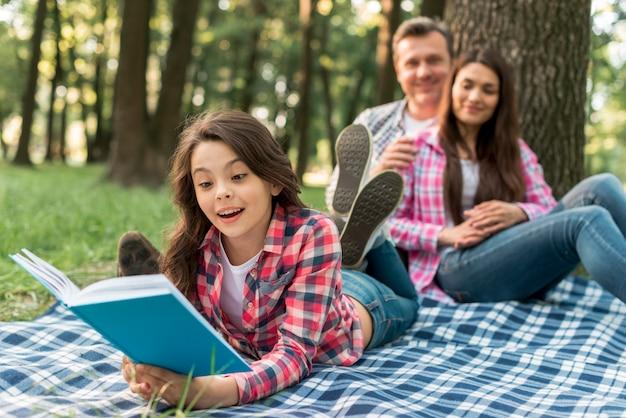 公園で本を読んで毛布の上に横たわる彼らのかわいい女の子の後ろに座っているカップル