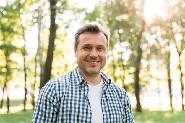 Портрет улыбающегося человека, стоящего в парке
