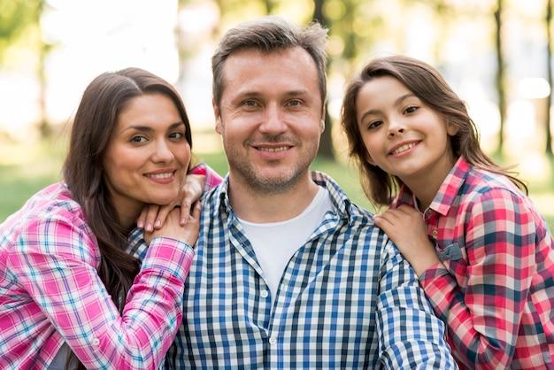 彼の妻と娘が公園でカメラ目線の笑みを浮かべて男