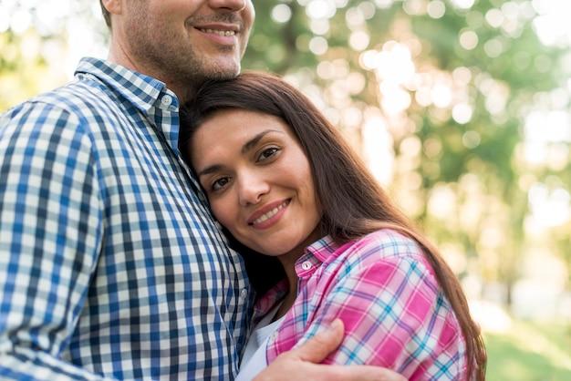 カメラを見て、屋外で彼女の夫を抱きしめる笑顔の女性