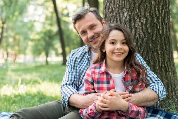 公園に坐っている間彼の娘を抱きしめる幸せな男