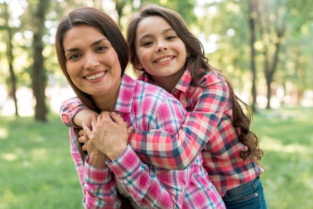 公園で彼女の娘におんぶを与える母親を笑顔