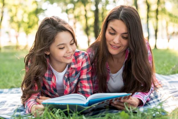 母と娘が一緒に本を読んで毛布の上に横たわる