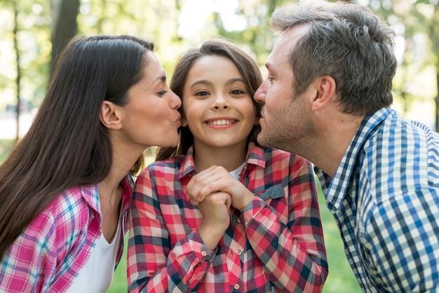 親が庭で彼らのかわいい娘にキス