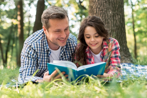 幸せな父と娘が公園で一緒に本を読んで