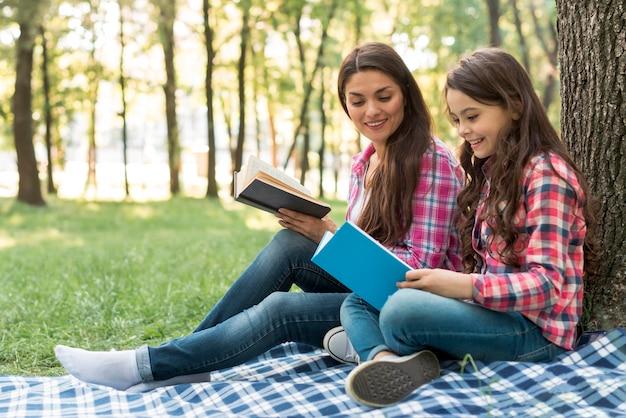 公園に座っている間彼女の娘によって保持されている本を見て笑顔の女性