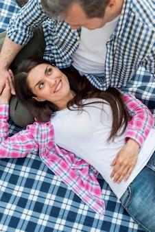 お互いを見て男の膝の上に横たわる幸せな女