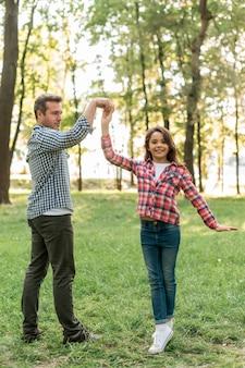 幸せな父と娘が庭で踊って